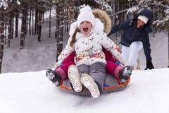 愉快的小女孩尖叫与欢欣,滚动与雪小山 免版税库存照片