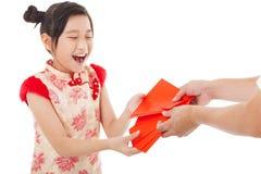 愉快的小女孩接受了红色信封 免版税库存图片