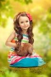 愉快的小女孩用兔子。贺卡 库存照片