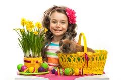 愉快的小女孩用复活节兔子和鸡蛋 免版税库存图片