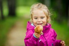 愉快的小女孩用蘑菇 图库摄影