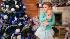 愉快的小女孩跳舞在装饰壁炉附近的一个圣诞节假日,与玩偶的小女孩跳舞, bobblehead 股票录像