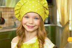 愉快的小女孩,厨师制服 免版税库存照片