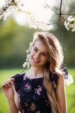 愉快的小姐和开花的树 免版税图库摄影