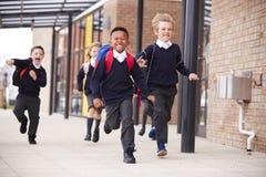 愉快的小学孩子,佩带的校服和背包,运行在他们的教学楼之外的一个走道,正面图, 免版税库存照片