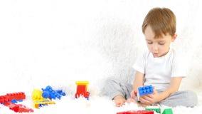 愉快的小孩坐长沙发,使用在色的块,坐白色背景 影视素材