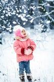 愉快的小孩女孩在一个美丽的多雪的冬天森林里 图库摄影