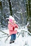 愉快的小孩女孩在一个美丽的多雪的冬天森林里 免版税图库摄影