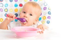 愉快的小孩子吃自己与匙子 免版税图库摄影