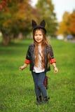愉快的小孩摆在为照相机的,笑和使用在自然步行的秋天的女婴户外 免版税库存图片