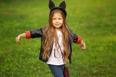 愉快的小孩摆在为照相机的,笑和使用在自然步行的秋天的女婴户外 库存照片