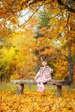 愉快的小孩,笑和使用在自然步行的秋天的女婴户外 免版税库存图片