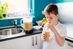 愉快的小男孩喝着自制水果鸡尾酒 免版税库存照片
