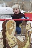 愉快的小男孩在冬天乘坐环形交通枢纽 库存图片