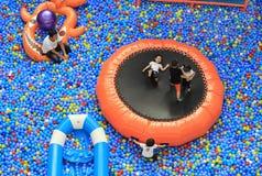 愉快的小男孩在多彩多姿的小球大堆放置  免版税图库摄影