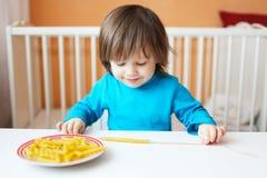 愉快的小男孩在家做了通心面小珠 免版税库存图片