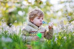 愉快的小男孩在有开花的白花的春天庭院里 免版税库存图片
