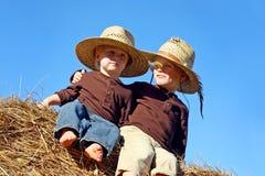 愉快的小男孩坐干草捆 免版税库存图片
