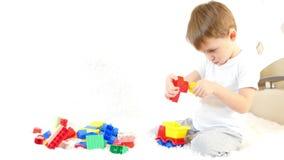 愉快的小男孩坐长沙发,使用在色的块,坐白色背景 影视素材