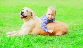 愉快的小男孩孩子和金毛猎犬狗在夏天公园的草一起使用 免版税库存照片