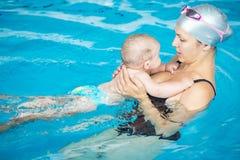 愉快的小男孩获得与他的母亲的乐趣在游泳池 免版税图库摄影