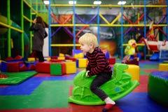 愉快的小男孩获得与塑料玩具摇摆/卖力摩托车的乐趣在戏剧中心 免版税库存照片
