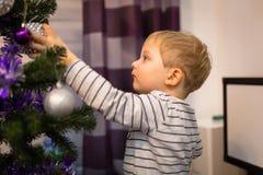 愉快的小男孩装饰圣诞树 免版税库存图片