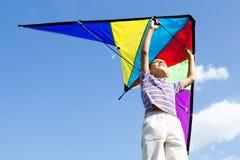愉快的小男孩飞行风筝入蓝天 免版税库存照片