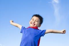 愉快的小男孩仿效超级英雄并且张开有蓝天的胳膊 免版税图库摄影
