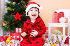 愉快的小男孩画象圣诞老人帽子的在圣诞树附近 库存图片