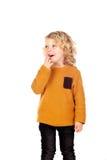 愉快的小白肤金发的儿童whith黄色球衣 免版税库存照片