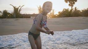 愉快的小的5-7使用在海洋水波的岁白种人女孩田园诗特写镜头射击在异乎寻常的日落海滩附近 股票视频