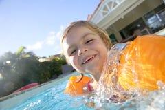 愉快的小的gril游泳iwith臂章n游泳池 库存图片