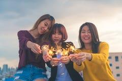 愉快的小组亚洲女朋友享用并且演奏闪烁发光物在屋顶上面党在晚上日落 免版税库存照片