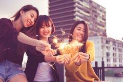 愉快的小组亚洲女朋友享用并且演奏闪烁发光物在屋顶 免版税库存照片