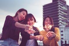 愉快的小组亚洲女朋友享用并且演奏闪烁发光物在屋顶 库存图片