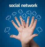 愉快的小组与社会网络标志和象的手指面带笑容 图库摄影
