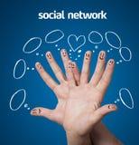 愉快的小组与社会网络标志和象的手指面带笑容 免版税图库摄影