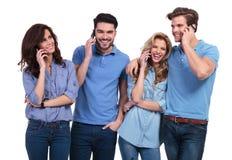 愉快的小组偶然人民谈话在他们的电话 免版税库存照片