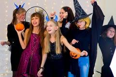 愉快的小组少年在万圣夜服装跳舞 免版税库存照片