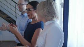 愉快的小组拍手在办公室的商人 影视素材