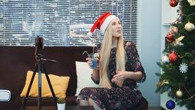 愉快的少女侧视图圣诞老人帽子录音录影的由在三脚架的智能手机 影视素材
