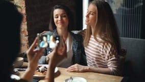 愉快的少女获得乐趣在与智能手机摆在的咖啡馆照相 股票录像