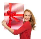 愉快的少妇举行红色圣诞节包裹了礼物当前smilin 免版税库存图片