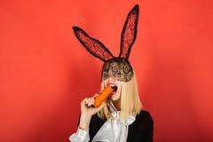 愉快的少妇佩带的兔宝宝耳朵和食用复活节彩蛋 微笑复活节 库存图片