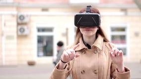愉快的少妇佩带网际空间虚拟现实耳机玻璃获得乐趣外面在街道上在米黄外套的技术vr 影视素材