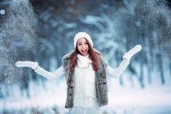 愉快的少妇使用与室外的雪 蓝色分行休息日霜谎言天空雪结构树冬天 免版税库存图片