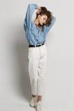 愉快的少妇全长画象,摆在斜纹布衬衣 免版税图库摄影