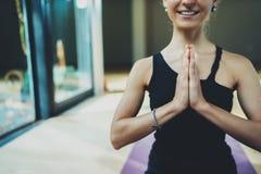 愉快的少妇前面画象在一个训练大厅里时思考,当实践瑜伽 查出的黑色概念自由 平静和 免版税库存图片