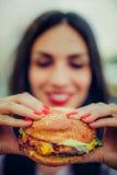 愉快的少妇吃鲜美快餐汉堡 库存图片